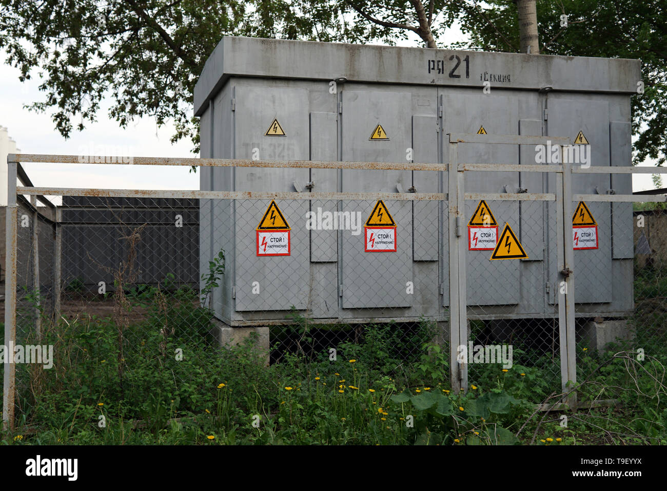 Outdoor electric power thansformer box with yellow hazard signs Stock Photo