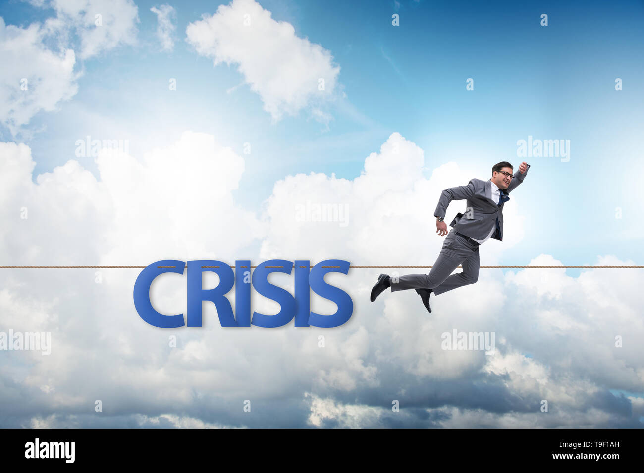 Crisis concept with businessman walking on tight rope - Stock Image