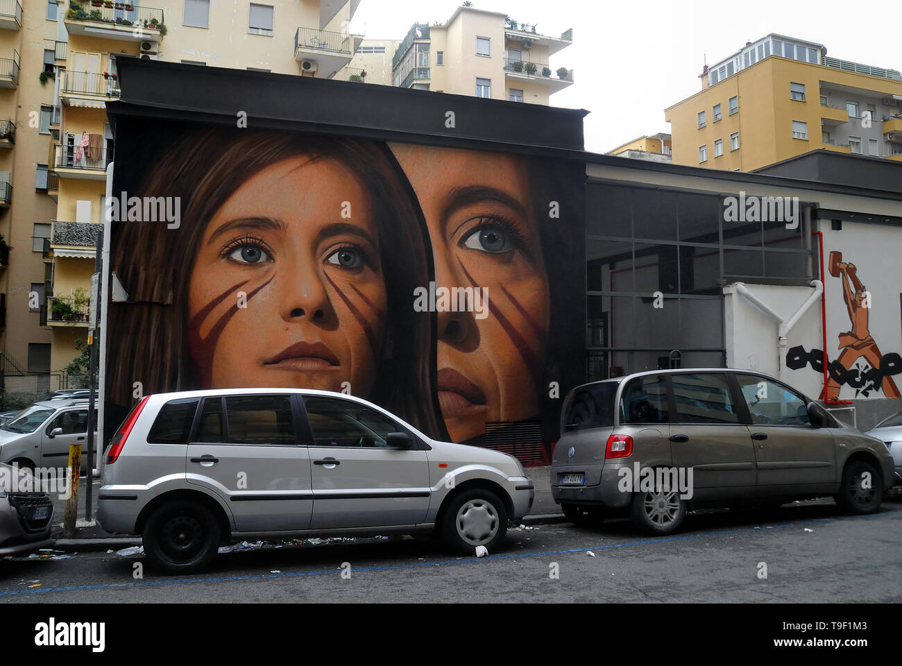 Jorit Agoch, 28, is Neapolitan street artist of international renown, Neapolitan father and Dutch mother. He creates giant murals on the facades of suburban buildings around the world. His works are present in Buenos Aires, Cochabamba, Aruba, Santiago de Chile, New York, Miami, Las Vegas, Sacramento, San Francisco, Shenzhen, Gaza. In Italy Jorit is mainly active in Naples where he makes huge paintings on blind facades of suburban buildings and also in the historic center. Naples, Vomero residential quarter, Jorit painting of Ilaria Cucchi, the sister of Stefano Cucchi. Stefano was killed in th - Stock Image