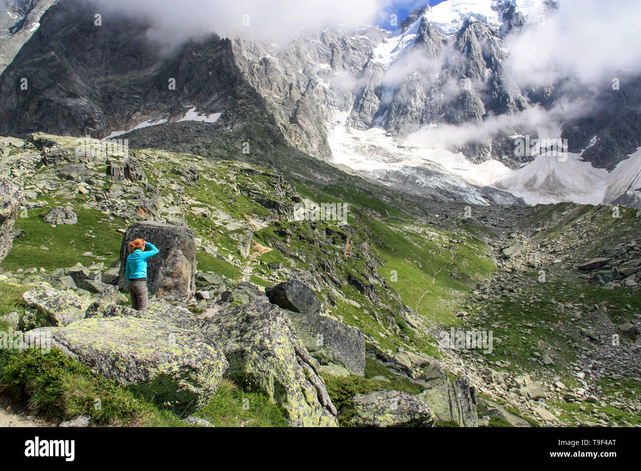 Redhead woman standing in between boulders and rocks exploring the Mont Blanc massif and looking towards the peak of the Aiguille du Midi in France Stock Photo