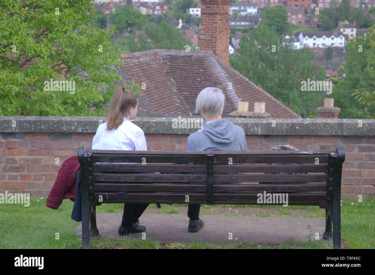 Rear view of a caucasian boy and girl sat on a bench in Bridgnorth, Shropshire, uk - Stock Image
