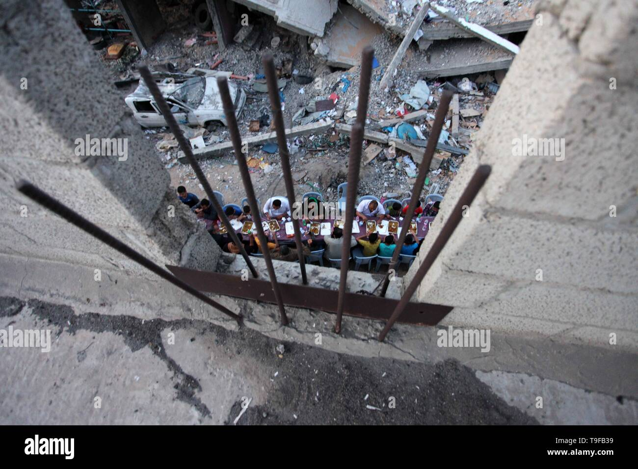 Gaza City, Gaza Strip, Palestinian Territory. 18th May, 2019. Palestinian families break their fast next to a destroyed building during recent confrontation between Hamas and Israel, during the Muslim holy fasting month of Ramadan, in Gaza city on May 18, 2019 Credit: Mahmoud Ajjour/APA Images/ZUMA Wire/Alamy Live News - Stock Image