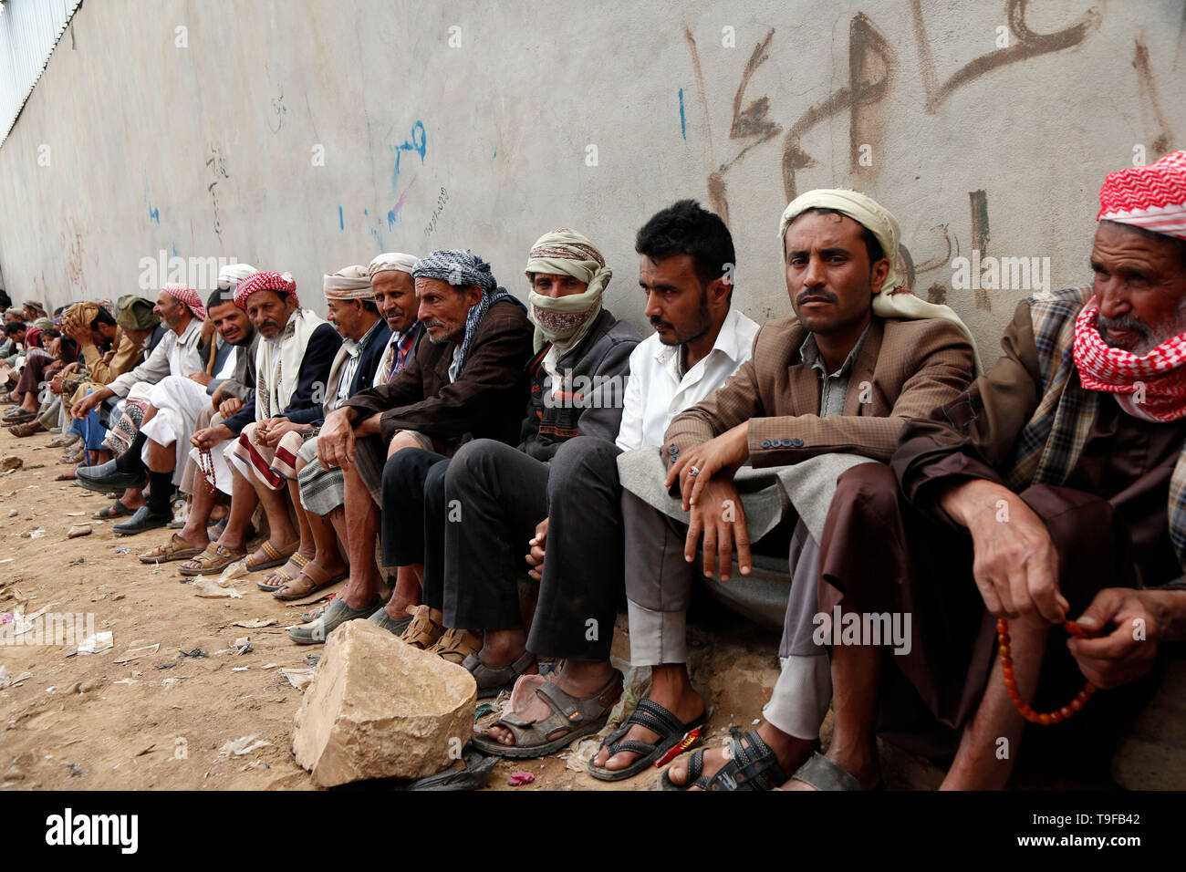 Sanaa, Yemen. 18th May, 2019. Yemenis wait to get food from a charity foundation in Sanaa, Yemen, on May 18, 2019. Ten million Yemenis are still reliant on emergency food assistance to survive, UN Under-Secretary-General for Humanitarian Affairs and Emergency Relief Coordinator Mark Lowcock told the Security Council on May 15. Credit: Mohammed Mohammed/Xinhua/Alamy Live News Credit: Xinhua/Alamy Live News - Stock Image