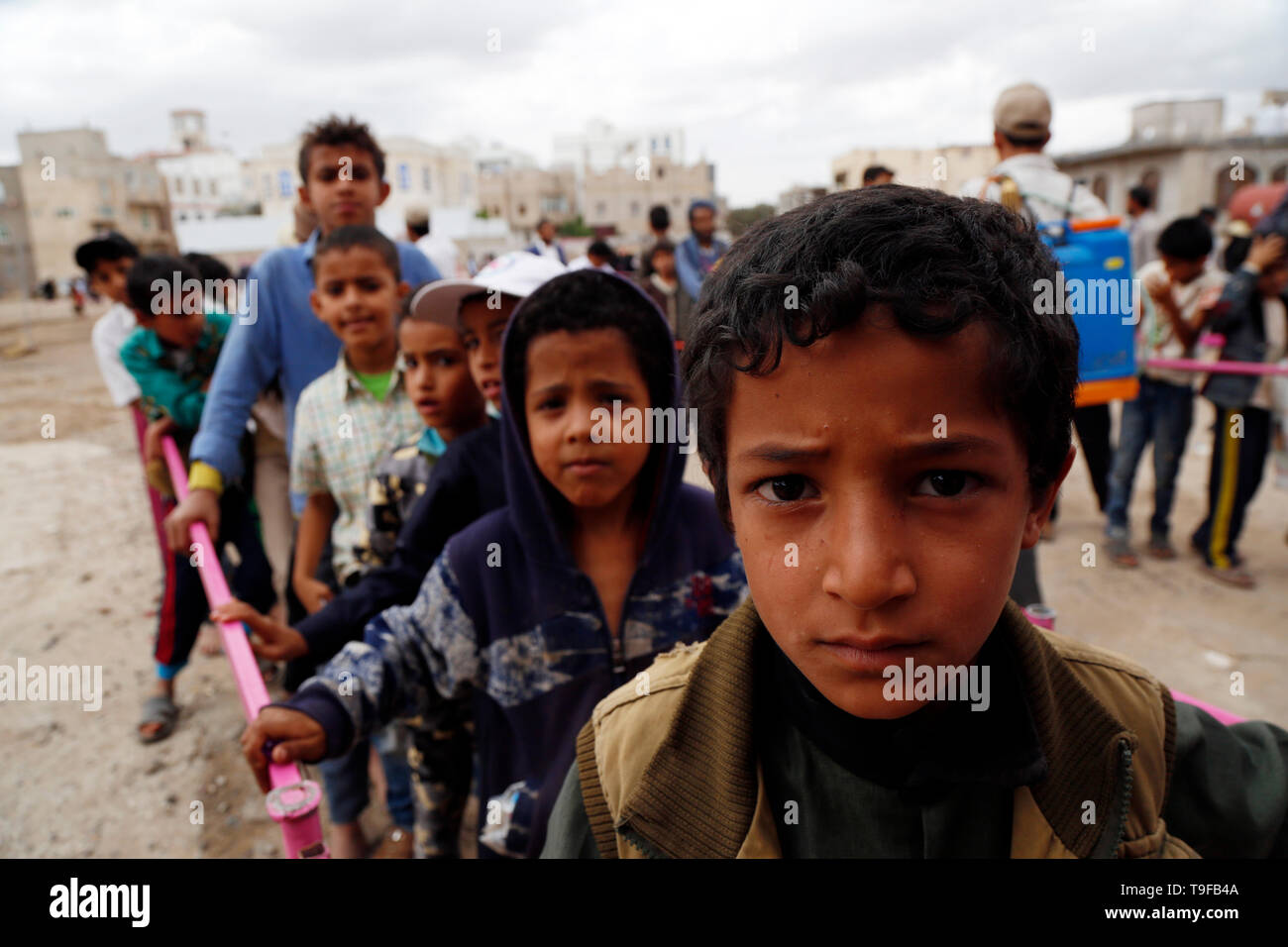 Sanaa, Yemen. 18th May, 2019. Yemeni children queue to get food from a charity foundation in Sanaa, Yemen, on May 18, 2019. Ten million Yemenis are still reliant on emergency food assistance to survive, UN Under-Secretary-General for Humanitarian Affairs and Emergency Relief Coordinator Mark Lowcock told the Security Council on May 15. Credit: Mohammed Mohammed/Xinhua/Alamy Live News Credit: Xinhua/Alamy Live News - Stock Image