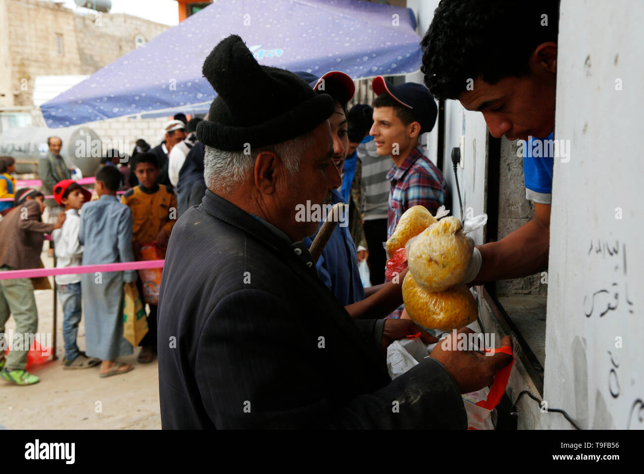 Sanaa, Yemen. 18th May, 2019. A man receives a bag of rice from a charity foundation in Sanaa, Yemen, on May 18, 2019. Ten million Yemenis are still reliant on emergency food assistance to survive, UN Under-Secretary-General for Humanitarian Affairs and Emergency Relief Coordinator Mark Lowcock told the Security Council on May 15. Credit: Mohammed Mohammed/Xinhua/Alamy Live News Credit: Xinhua/Alamy Live News - Stock Image