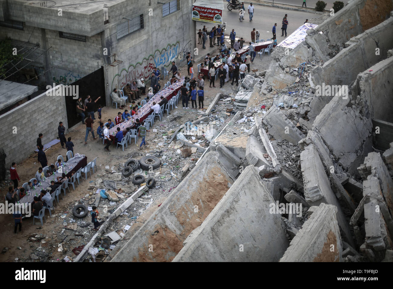 Gaza, Palestinian Territories. 19th May, 2019. Palestinian families break their fast during the Muslim holy fasting month of Ramadan, next to the remains of a building that was destroyed during Israeli air strikes. Credit: Mohammed Talatene/dpa/Alamy Live News - Stock Image