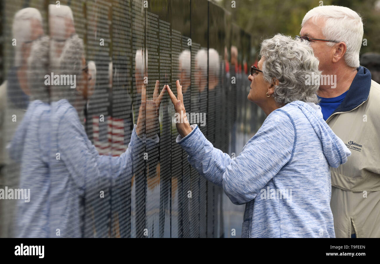 Racine, Wisconsin, USA. 18th May, 2019. LuAnn Tully, whose uncles served in Vietnam and survived the war, feels the texture of names on the wall as she visits the Moving Wall, a half-size replica of the Vietnam Veterans Memorial, in Racine, Wisconsin, Saturday May 18, 2019 with her husband Tim Tully. Forty-seven soldiers from Racine were killed during the war. The Moving Wall has been touring the United States for more than 30 years. Credit: Mark Hertzberg/ZUMA Wire/Alamy Live News - Stock Image
