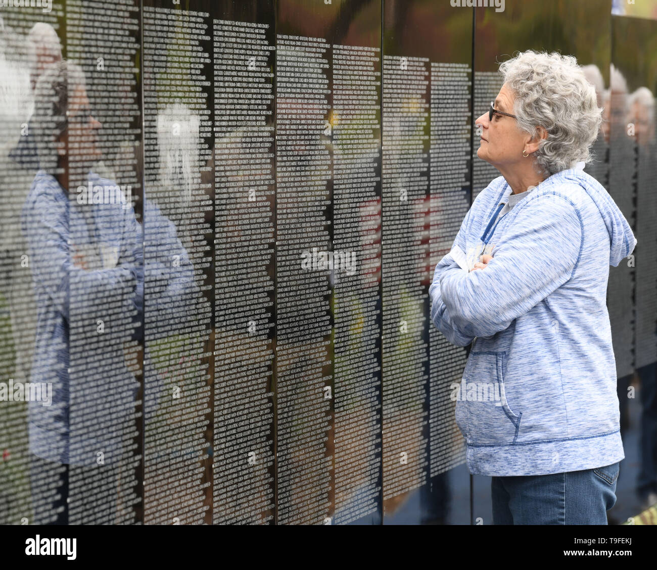 Racine, Wisconsin, USA. 18th May, 2019. LuAnn Tully, whose uncles served in Vietnam and survived the war, visits the Moving Wall, a half-size replica of the Vietnam Veterans Memorial, in Racine, Wisconsin, Saturday May 18, 2019. Forty-seven soldiers from Racine were killed during the war. The Moving Wall has been touring the United States for more than 30 years. Credit: Mark Hertzberg/ZUMA Wire/Alamy Live News - Stock Image