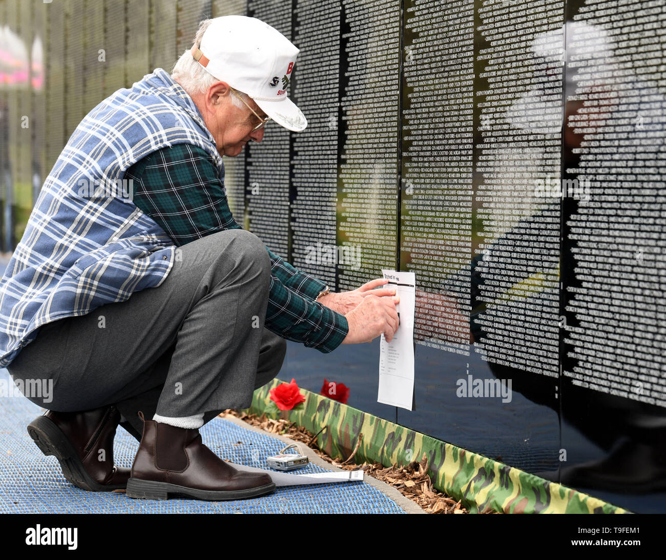 Racine, Wisconsin, USA. 18th May, 2019. Andris Vinakmens etches the names of his high school classmate Tony Albasio at the Moving Wall, a half-size replica of the Vietnam Veterans Memorial, in Racine, Wisconsin, Saturday May 18, 2019. Another classmate, Ed Wyatt, also died in Vietnam. The three served on B-52 bombers. Forty-seven soldiers from Racine were killed during the war. The Moving Wall has been touring the United States for more than 30 years. Credit: Mark Hertzberg/ZUMA Wire/Alamy Live News - Stock Image