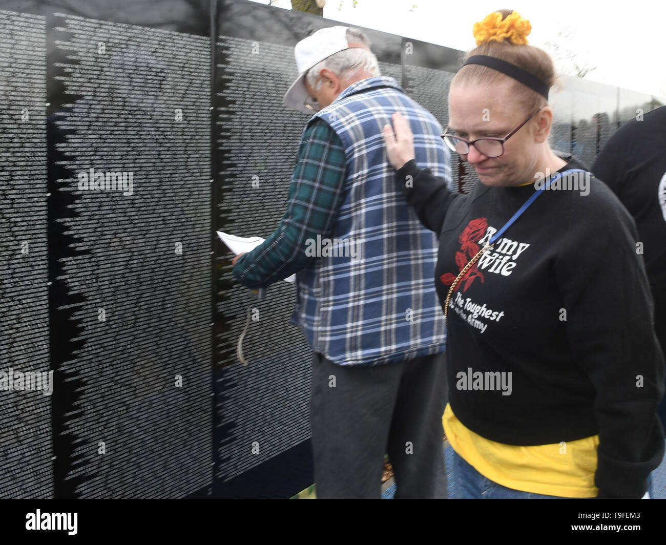 Racine, Wisconsin, USA. 18th May, 2019. A woman with a shirt that says 'Army Wife - The Toughest Job in the Army'' pats Vietnam veteran Andris Vinakmens as she passes by him at the Moving Wall, a half-size replica of the Vietnam Veterans Memorial, in Racine, Wisconsin, Saturday May 18, 2019. Forty-seven soldiers from Racine were killed during the war. The Moving Wall has been touring the United States for more than 30 years. Credit: Mark Hertzberg/ZUMA Wire/Alamy Live News - Stock Image