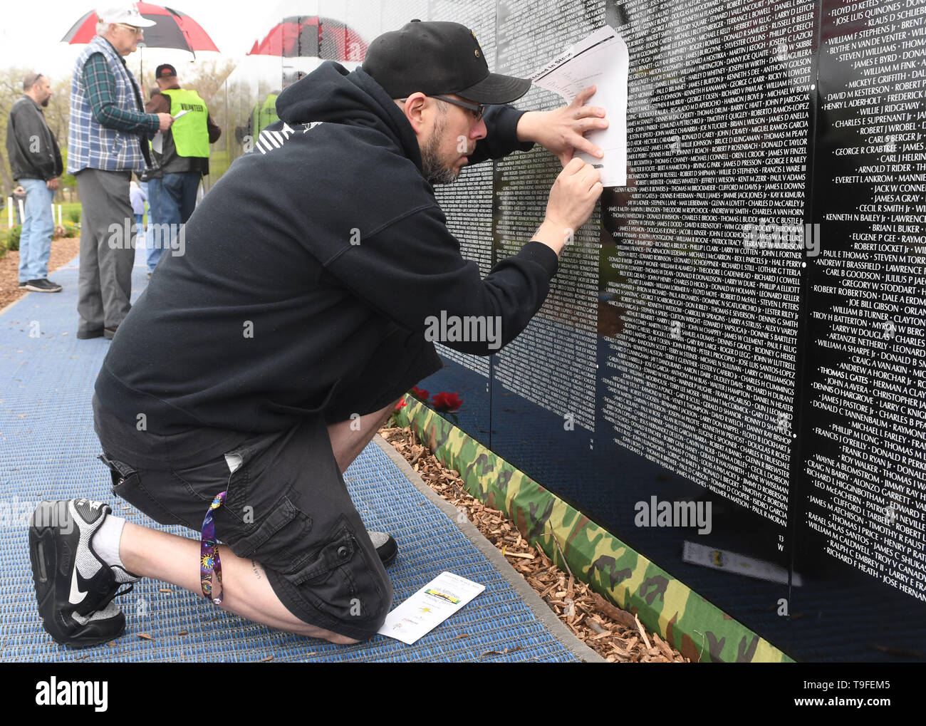 May 18, 2019 - Racine, Wisconsin, USA - Christian Woodard is emotional as he makes an etching of the name of Jerald Dale West and then removes his cap and bows his head at the Moving Wall, a half-size replica of the Vietnam Veterans Memorial, in Racine, Wisconsin, Saturday May 18, 2019. West, his half-brother's uncles, was killed in Vietnam January 31, 1970. Woodard was plans to send the etching to his half-brother. Forty-seven soldiers from Racine were killed during the war. The Moving Wall has been touring the United States for more than 30 years. (Credit Image: © Mark Hertzberg/ZUMA Wire) - Stock Image