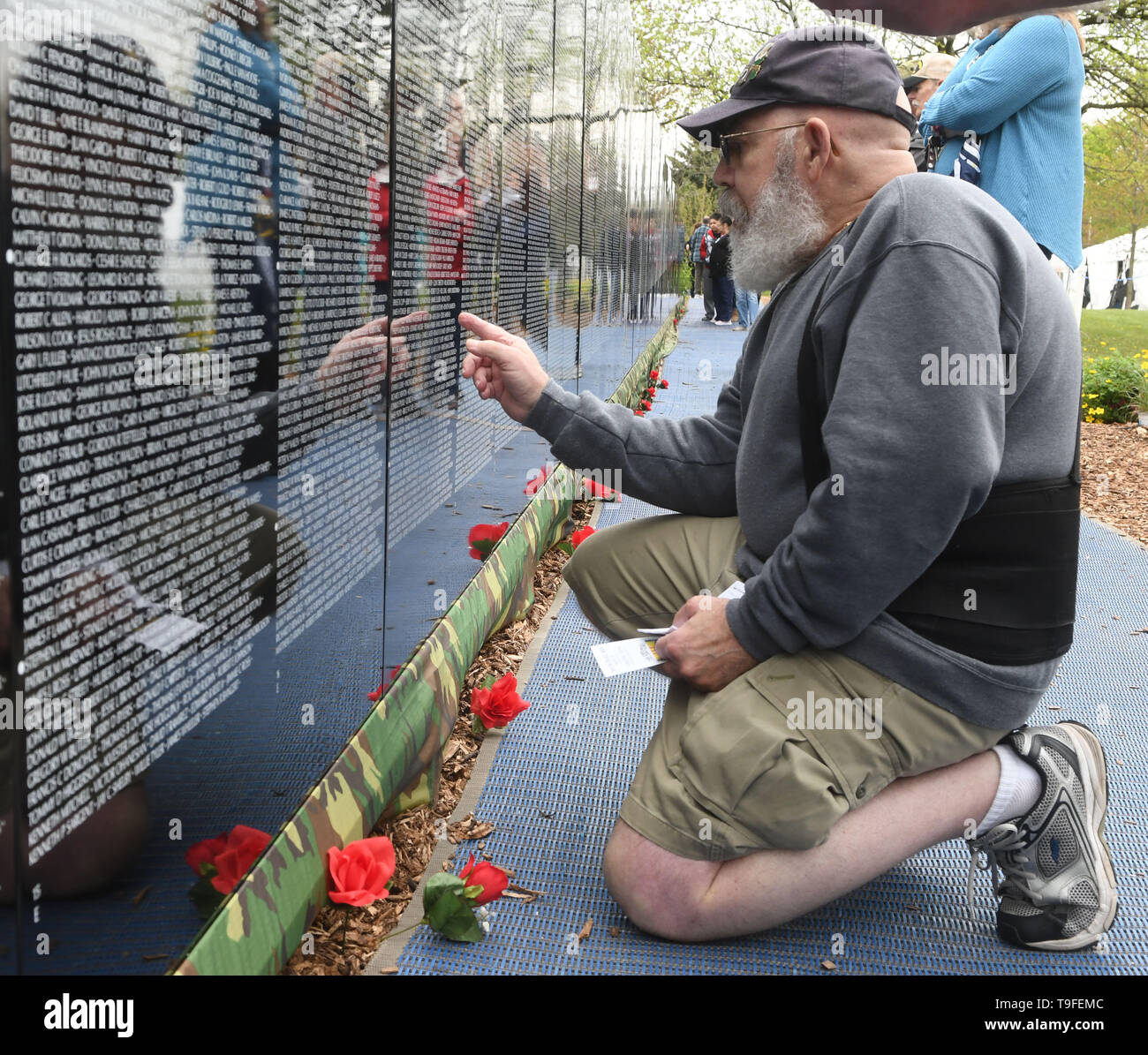 Racine, Wisconsin, USA. 18th May, 2019. Jack Berry looks for the name of Daniel Patrick, a high school classmate in the class of 1965, at the Moving Wall, a half-size replica of the Vietnam Veterans Memorial, in Racine, Wisconsin, Saturday May 18, 2019. He died on Berry's birthday. Forty-seven soldiers from Racine were killed during the war. The Moving Wall has been touring the United States for more than 30 years. Credit: Mark Hertzberg/ZUMA Wire/Alamy Live News - Stock Image