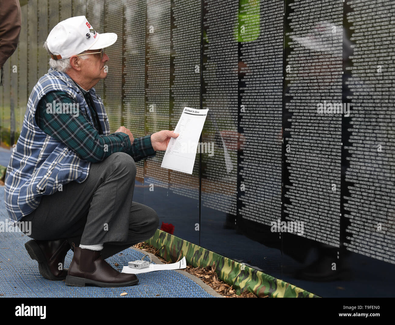 Racine, Wisconsin, USA. 18th May, 2019. Andris Vinakmens looks for the names of his high school classmates Ed Wyatt and Tony Albasio at the Moving Wall, a half-size replica of the Vietnam Veterans Memorial, in Racine, Wisconsin, Saturday May 18, 2019. The three served on B-52 bombers. Forty-seven soldiers from Racine were killed during the war. The Moving Wall has been touring the United States for more than 30 years. Credit: Mark Hertzberg/ZUMA Wire/Alamy Live News - Stock Image