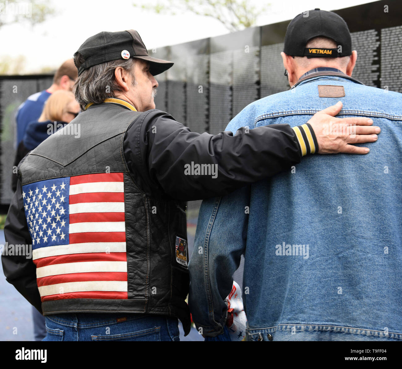 Racine, Wisconsin, USA. 18th May, 2019. An Army veteran who identifies himself only as 'Shorty, ' left, comforts Vietnam War veteran Ronald Hansen at the Moving Wall, a half-size replica of the Vietnam Veterans Memorial, in Racine, Wisconsin, Saturday May 18, 2019. Hansen, who served in the Army from 1968-69, told 'Shorty' of his desire to take a military Honor Flight. Forty-seven soldiers from Racine were killed during the war. The Moving Wall has been touring the United States for more than 30 years. Credit: Mark Hertzberg/ZUMA Wire/Alamy Live News - Stock Image