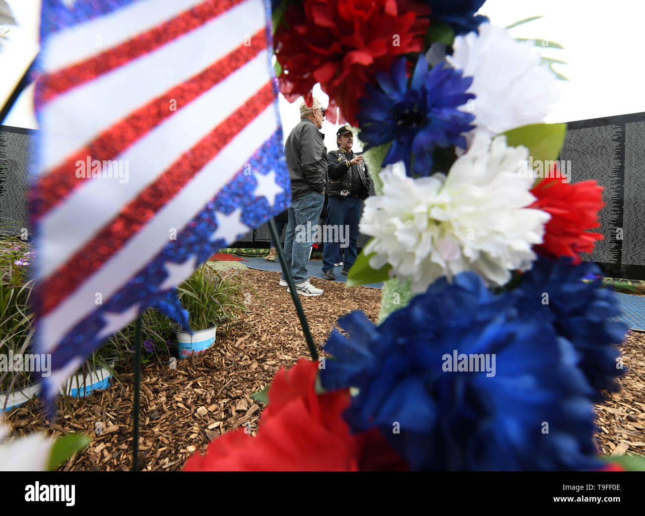 Racine, Wisconsin, USA. 18th May, 2019. Visitors to the Moving Wall, a half-size replica of the Vietnam Veterans Memorial, in Racine, Wisconsin, are framed by a wreath Saturday May 18, 2019. He died on Berry's birthday. Forty-seven soldiers from Racine were killed during the war. The Moving Wall has been touring the United States for more than 30 years. Credit: Mark Hertzberg/ZUMA Wire/Alamy Live News - Stock Image