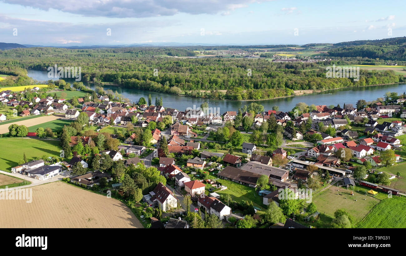 13 May 2019, Baden-Wuerttemberg, Büsingen am Hochrhein: The evening sun shines on the village of Büsingen on the High Rhine. In the background - behind the Rhine - Switzerland is to be longed for (recording with a drone). (to dpa 'European elections in the middle of Switzerland - German exclave Büsingen') Photo: Felix Kästle/dpa - Stock Image