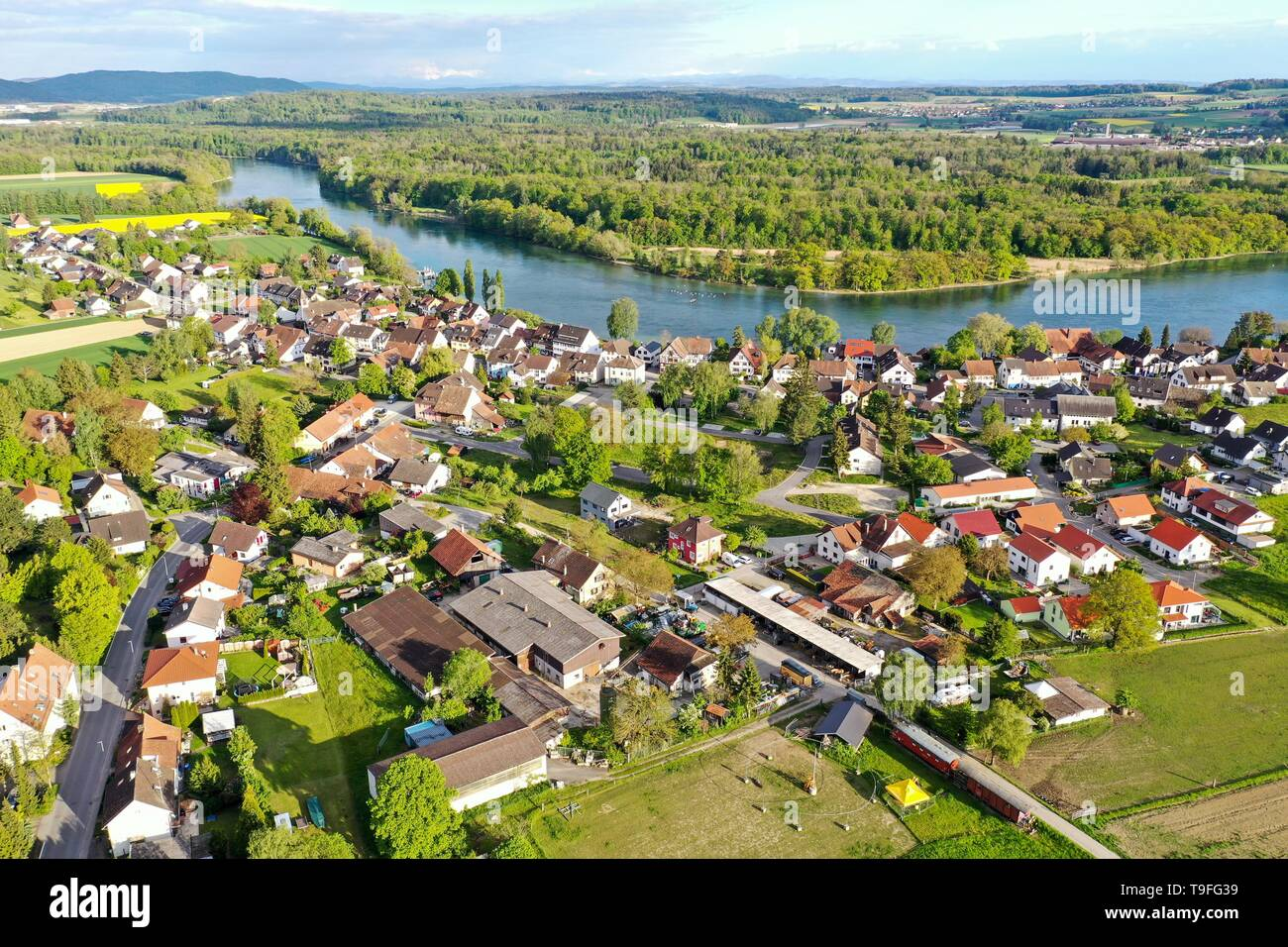12 March 2018, Baden-Wuerttemberg, Büsingen am Hochrhein: The evening sun shines on the village of Büsingen on the High Rhine. In the background - behind the Rhine - Switzerland is to be longed for (recording with a drone). Photo: Felix Kästle/dpa - Stock Image