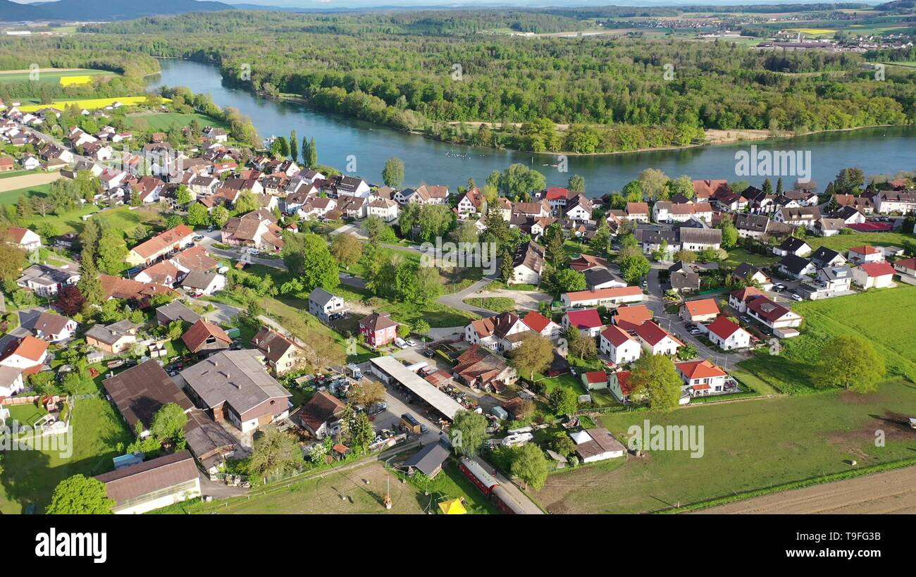 13 May 2019, Baden-Wuerttemberg, Büsingen am Hochrhein: The evening sun shines on the village of Büsingen on the High Rhine. In the background - behind the Rhine - Switzerland is to be longed for (recording with a drone). Photo: Felix Kästle/dpa - Stock Image