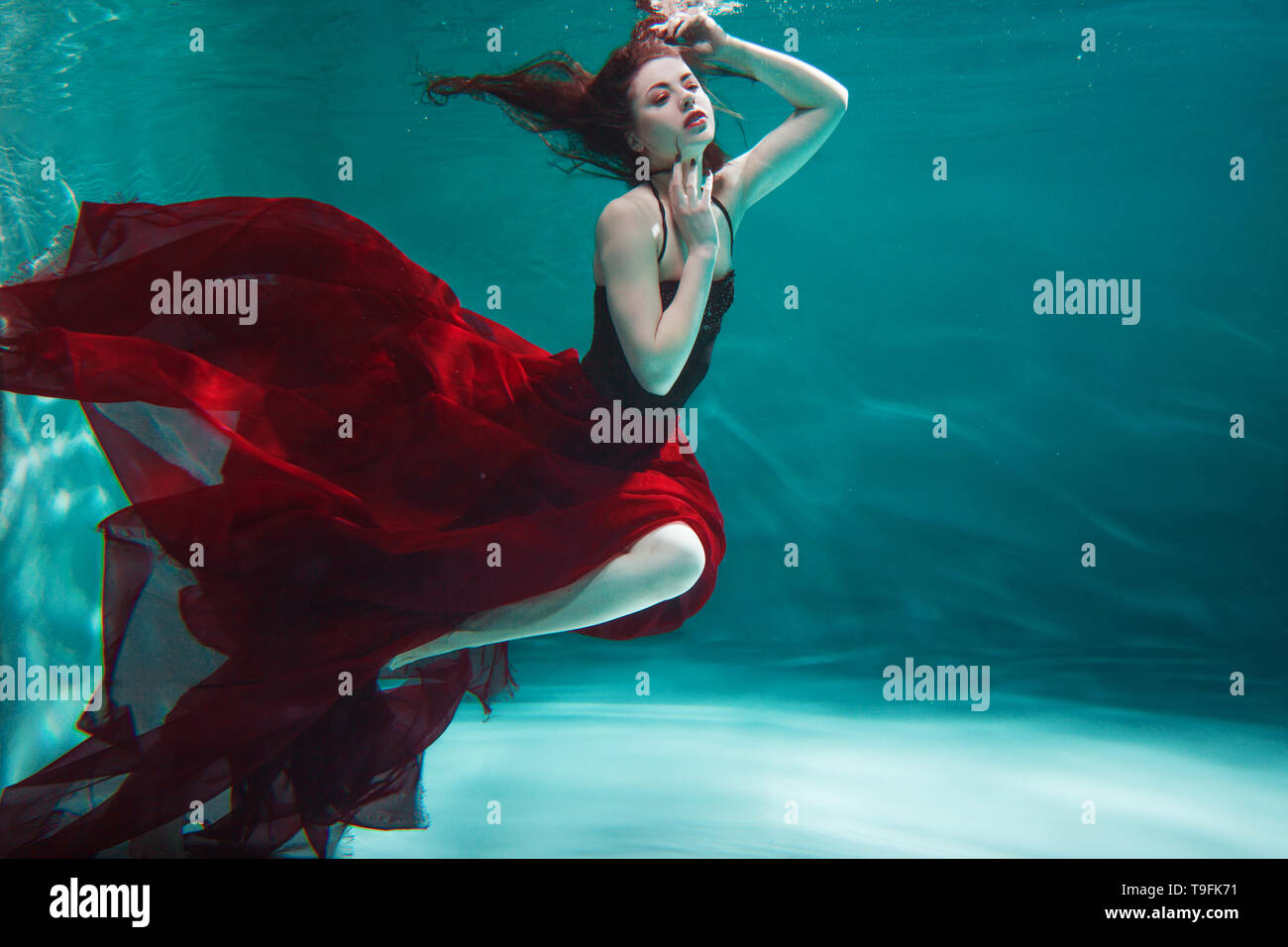 Beautiful young woman in a red dress swims under water. amazing Underwater beauty photo. - Stock Image