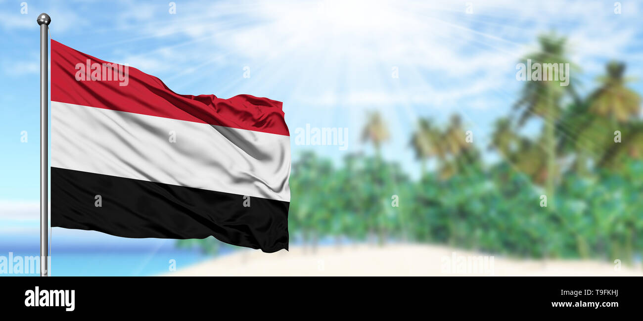 Waving Yemen flag in the sunny blue sky with summer beach background. Vacation theme, holiday concept. - Stock Image