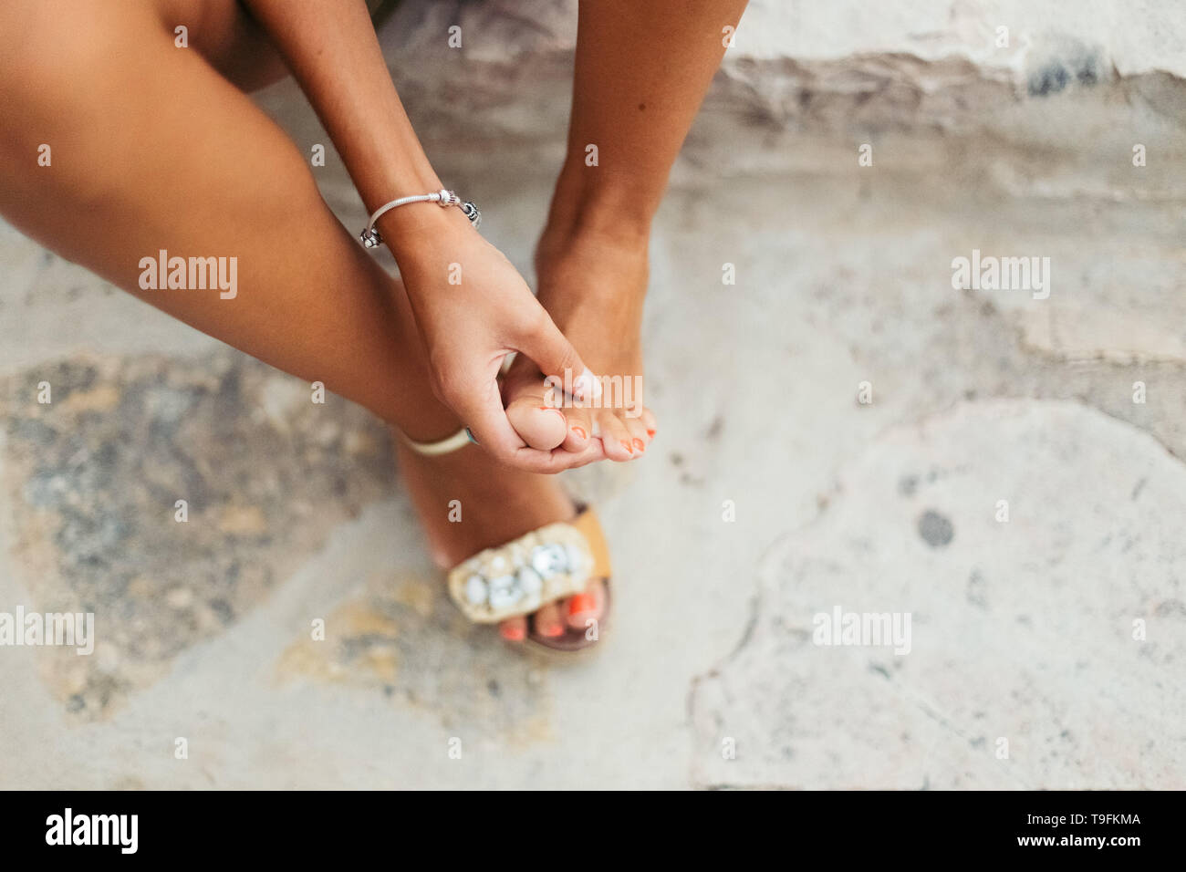 Tourist woman with sore feet and blisters checks her aching feet. Stock Photo