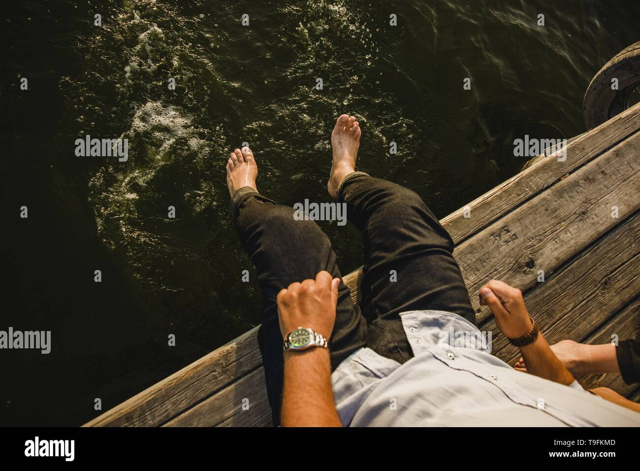 Male tourist refreshing his feet in the sea water, grain film added. - Stock Image