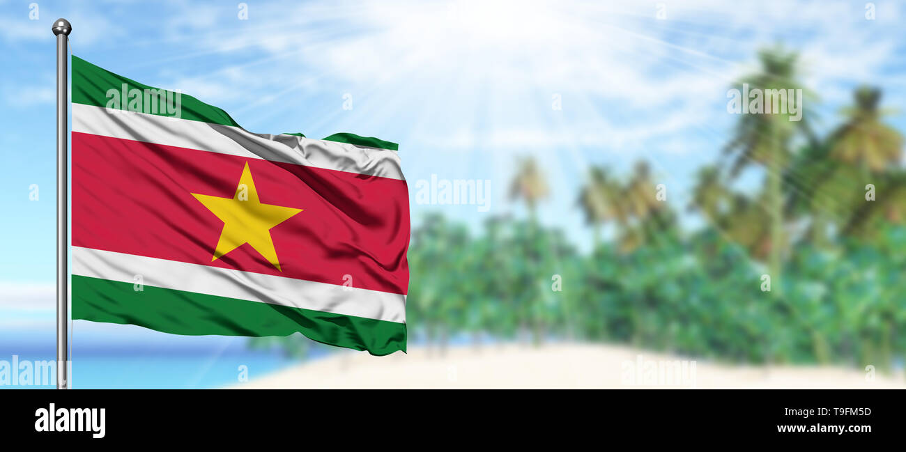 Waving Suriname flag in the sunny blue sky with summer beach background. Vacation theme, holiday concept. - Stock Image