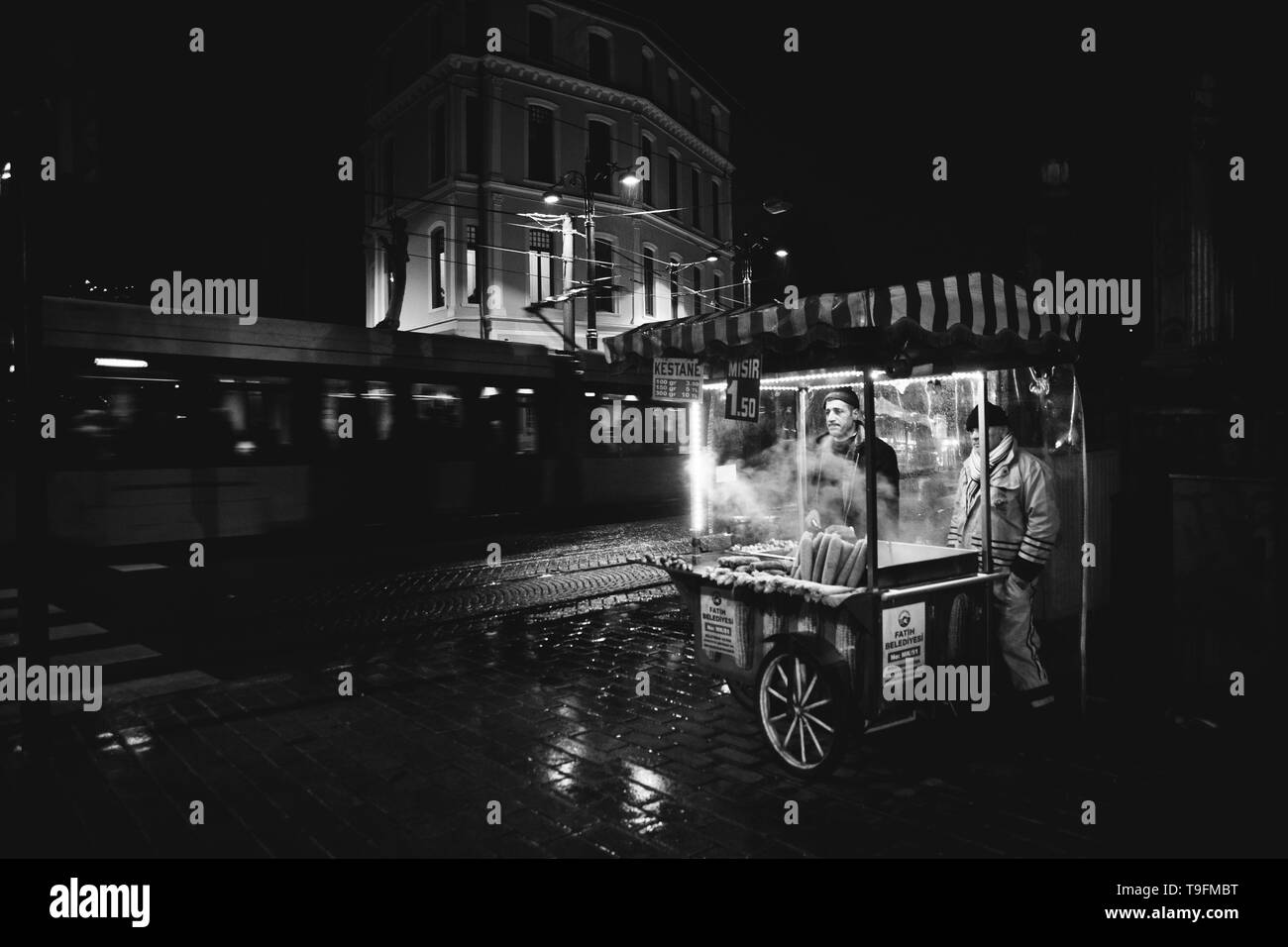 Istanbul, Turkey - April 11, 2012: Street vendor hot food, black and white night photography. - Stock Image