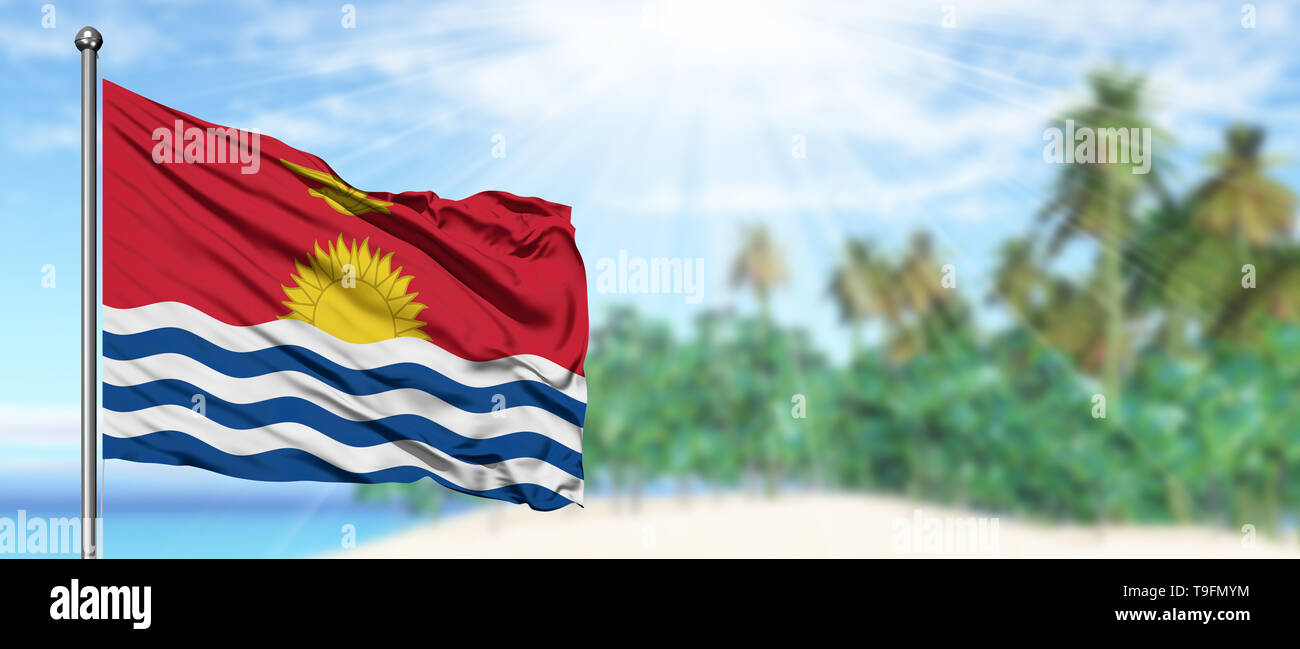 Waving Kiribati flag in the sunny blue sky with summer beach background. Vacation theme, holiday concept. - Stock Image