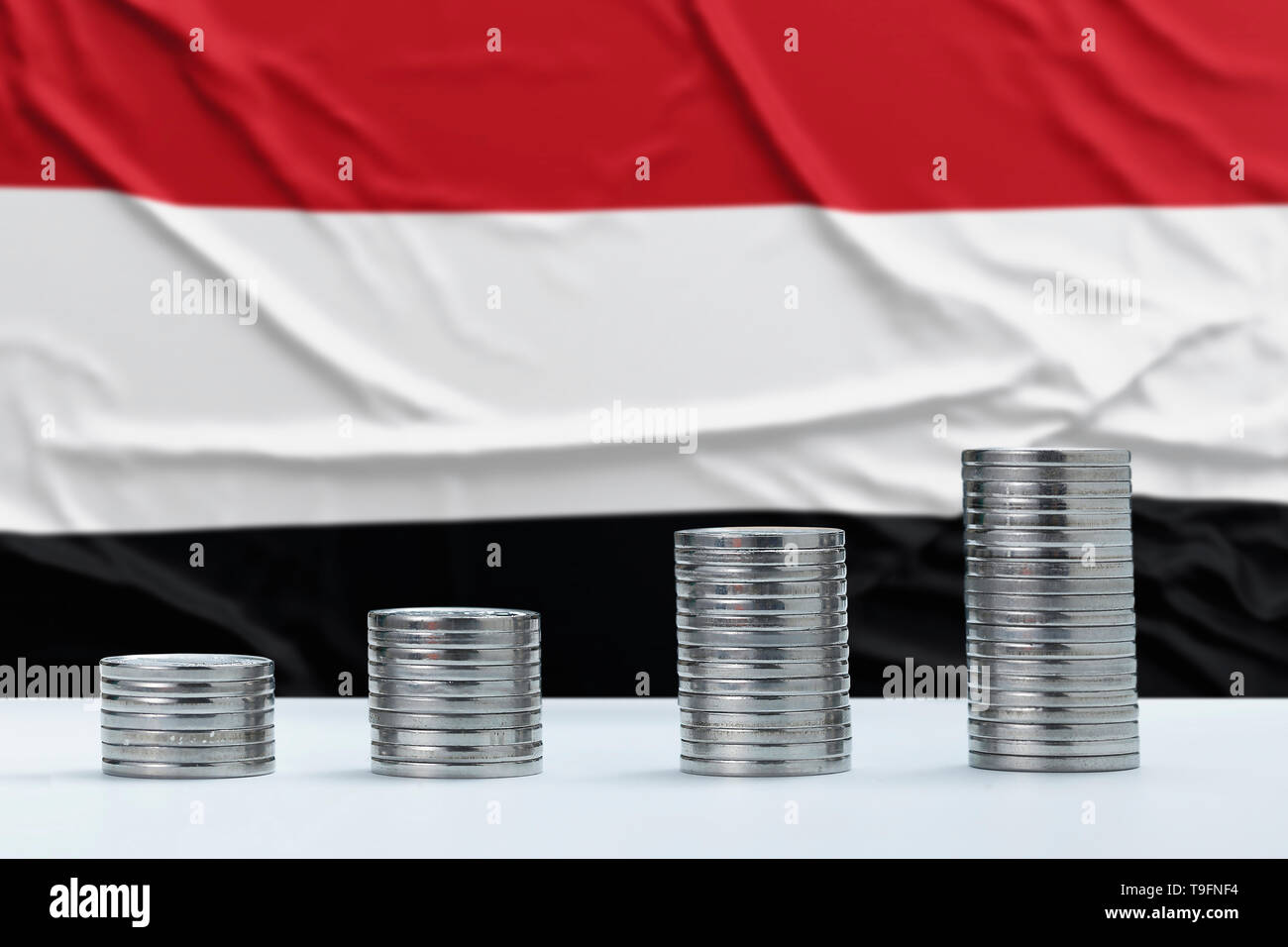 Wrinkled Yemen flag in the background with rows of coins for finance and business concept. Saving money. - Stock Image