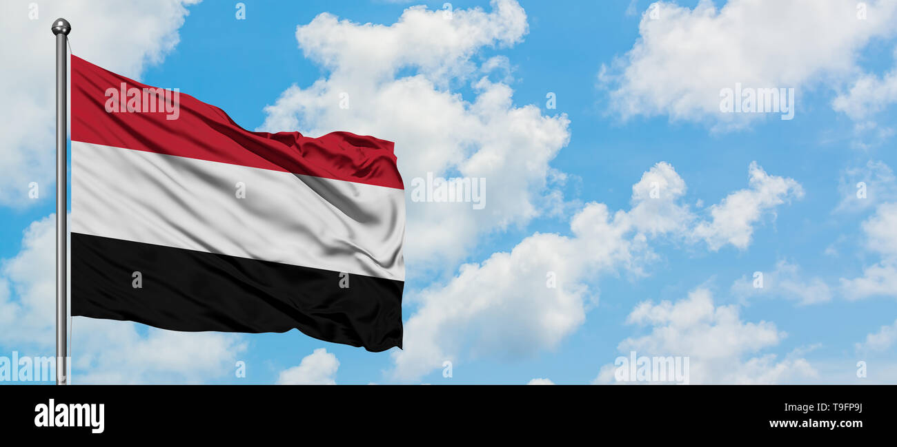 Yemen flag waving in the wind against white cloudy blue sky. Diplomacy concept, international relations. - Stock Image