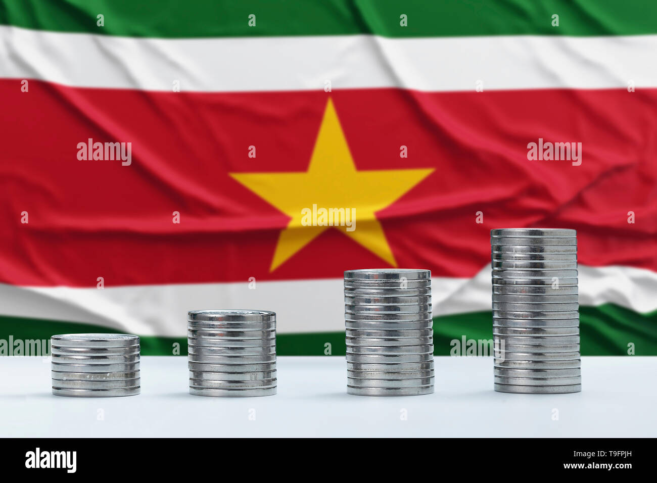 Wrinkled Suriname flag in the background with rows of coins for finance and business concept. Saving money. - Stock Image