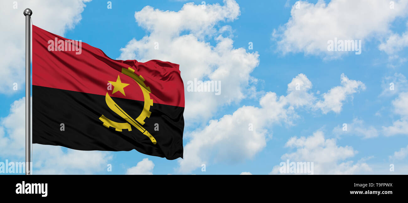 Angola flag waving in the wind against white cloudy blue sky. Diplomacy concept, international relations. - Stock Image