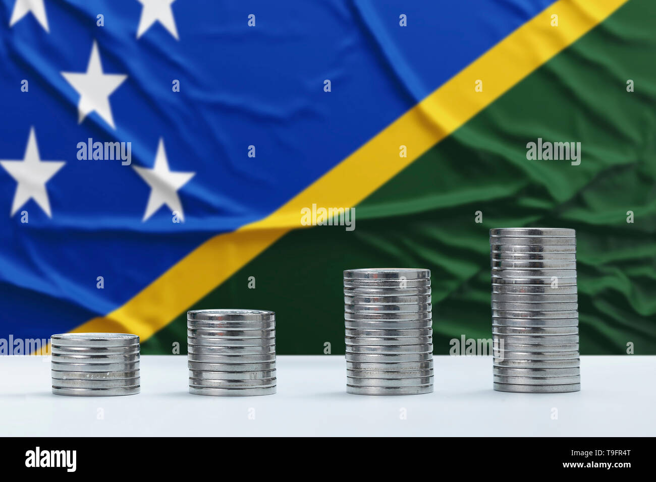 Wrinkled Solomon Islands flag in the background with rows of coins for finance and business concept. Saving money. - Stock Image