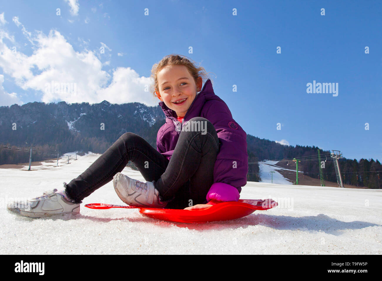 Smiling girl having fun on a bum board - Stock Image