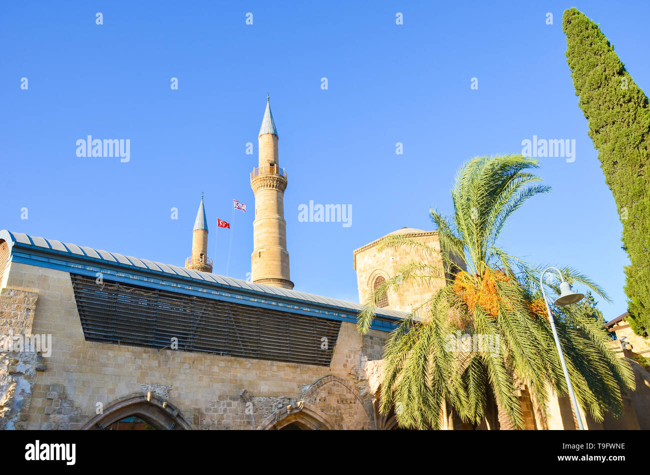Muslim Selimiye Mosque in Nicosia, Northern Cyprus taken from below with blue sky and green trees around. Originally Roman Catholic Cathedral - Stock Image