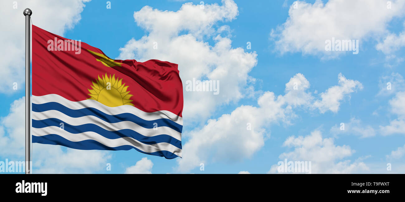 Kiribati flag waving in the wind against white cloudy blue sky. Diplomacy concept, international relations. - Stock Image