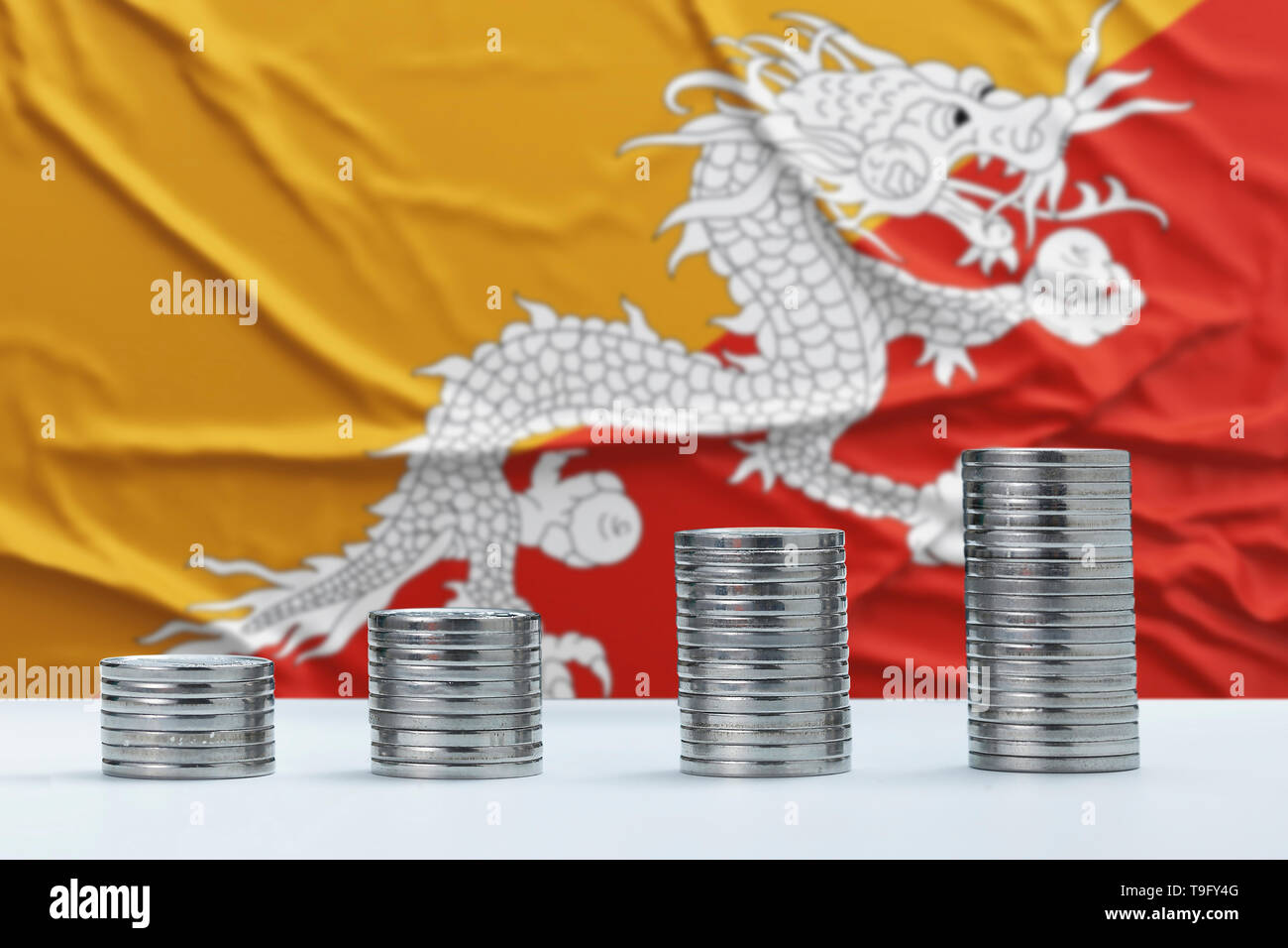 Wrinkled Bhutan flag in the background with rows of coins for finance and business concept. Saving money. - Stock Image
