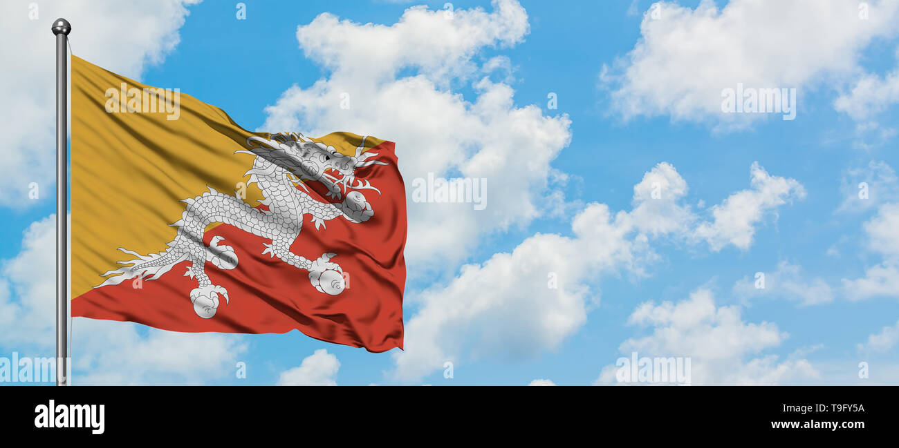 Bhutan flag waving in the wind against white cloudy blue sky. Diplomacy concept, international relations. - Stock Image