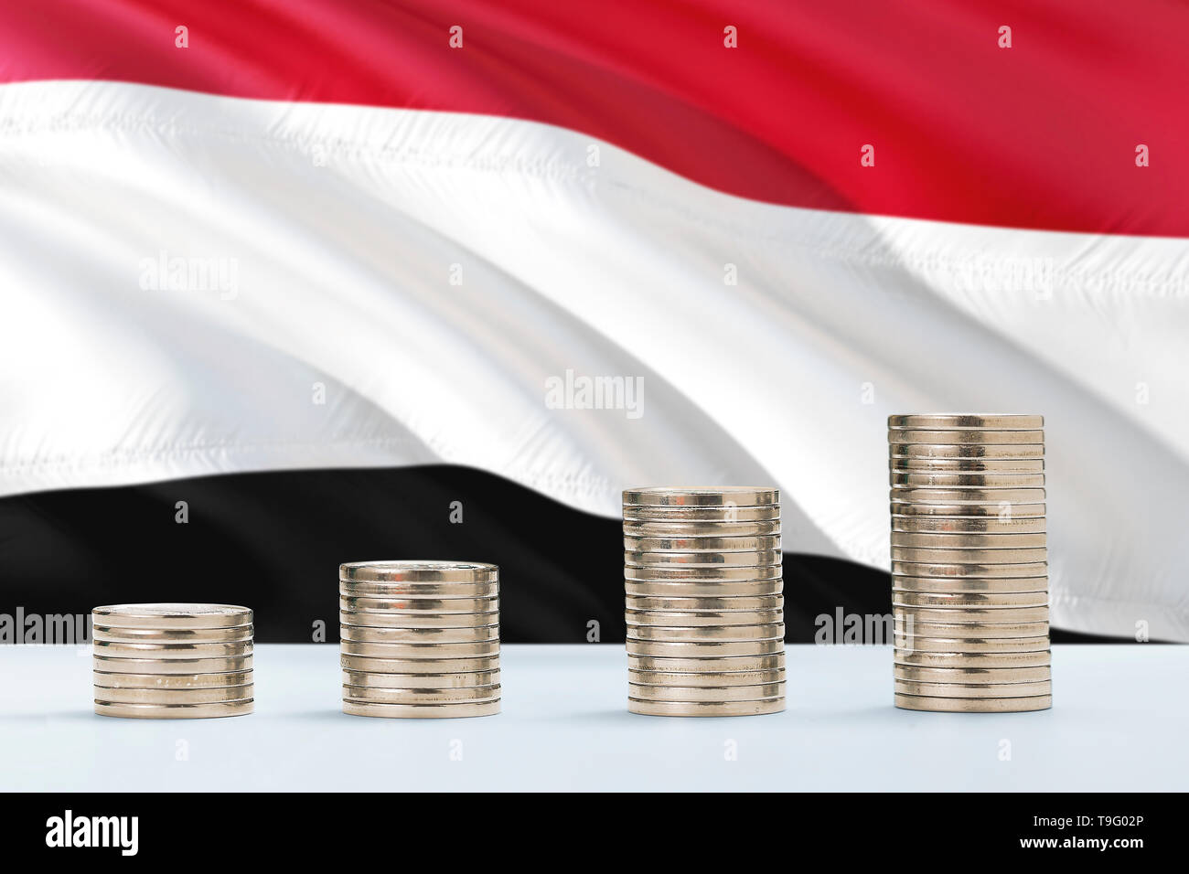 Yemen flag waving in the background with rows of coins for finance and business concept. Saving money. - Stock Image