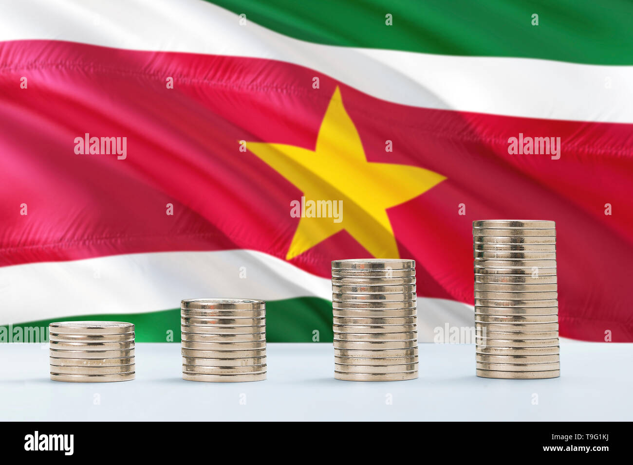 Suriname flag waving in the background with rows of coins for finance and business concept. Saving money. - Stock Image