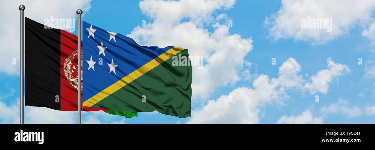 Afghanistan and Solomon Islands flag waving in the wind against white cloudy blue sky together. Diplomacy concept, international relations. - Stock Image