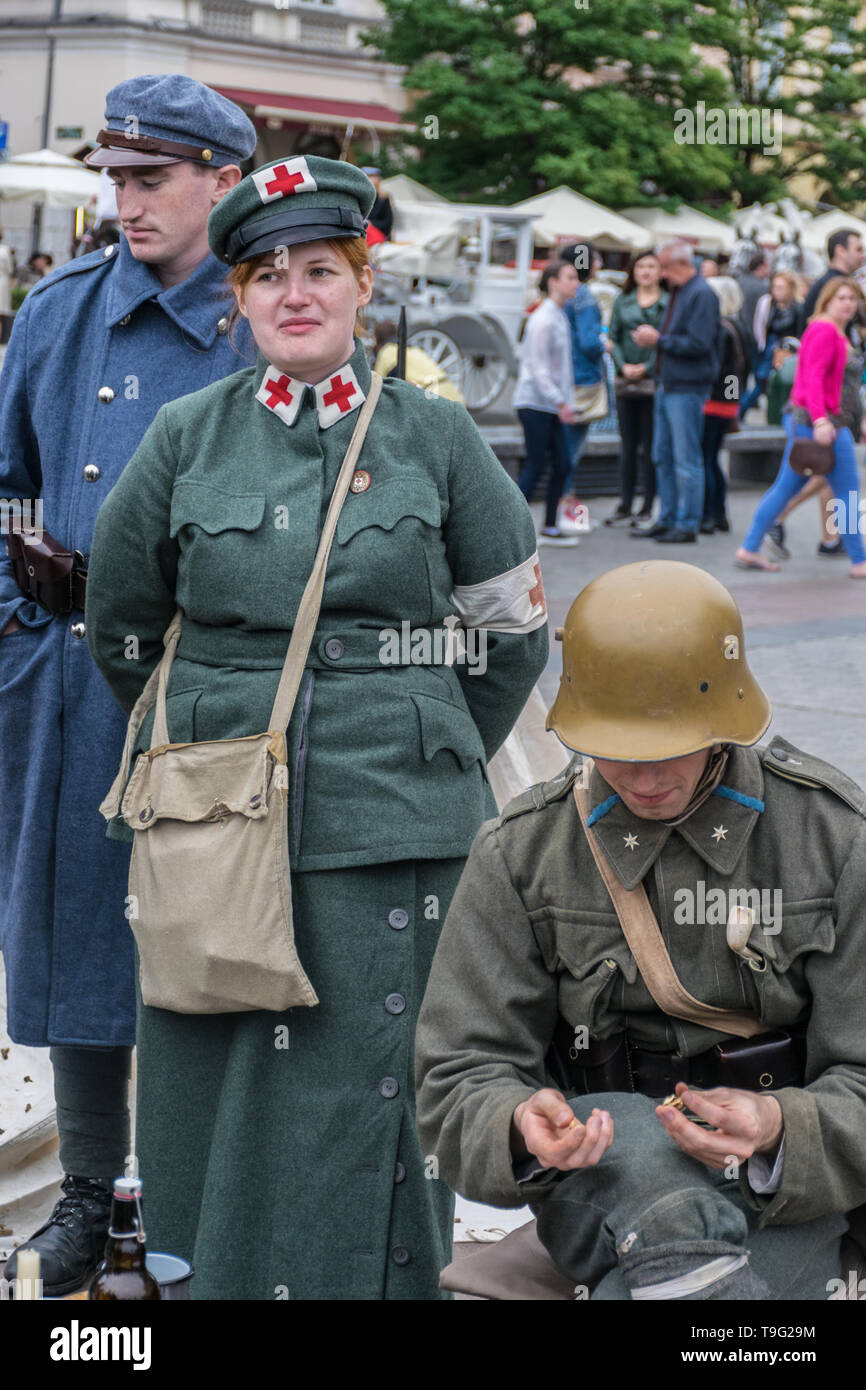 Krakow, Poland - September 23, 2018:   Men and woman dressed in Polish uniforms from World War I among tourists at krakow's main square  - Stock Photo