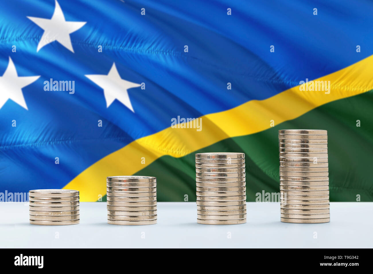Solomon Islands flag waving in the background with rows of coins for finance and business concept. Saving money. - Stock Image