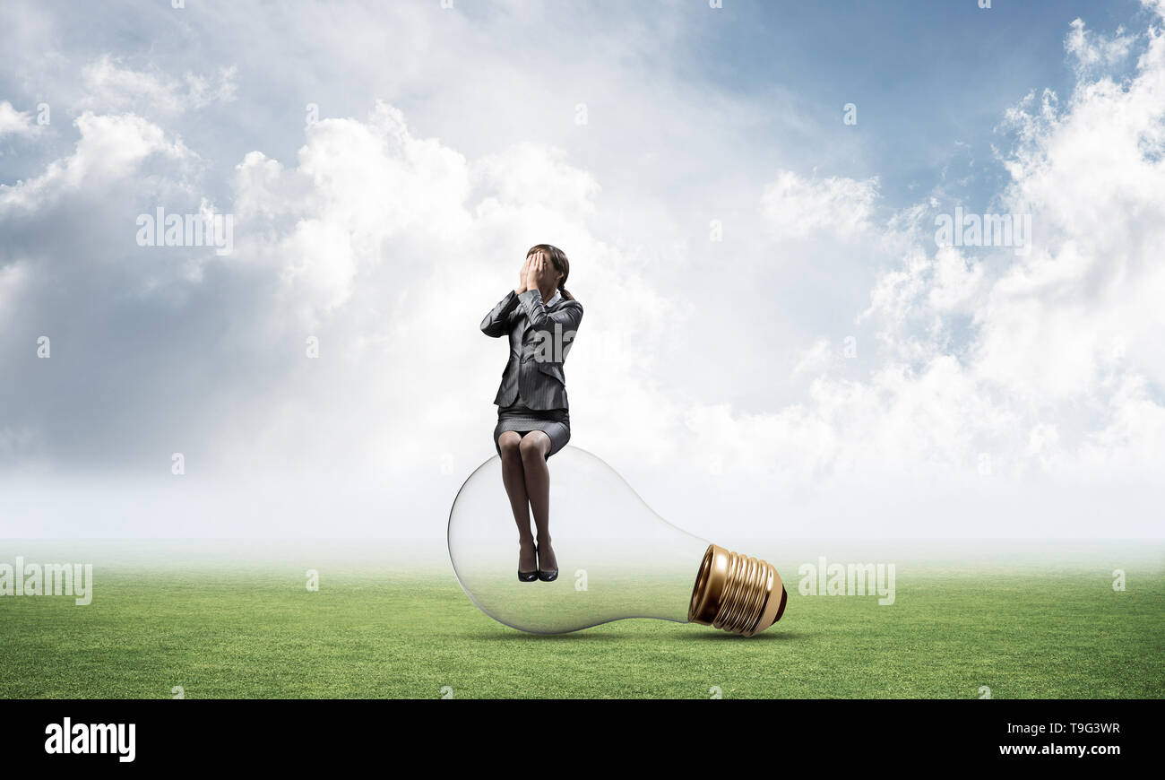 Young woman sitting on big light bulb - Stock Image