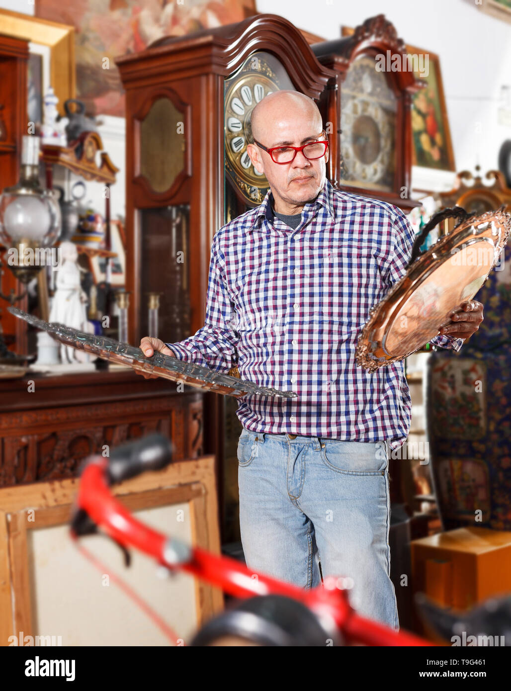 Interested adult male collector of rare items choosing ancient things in antique shop - Stock Image