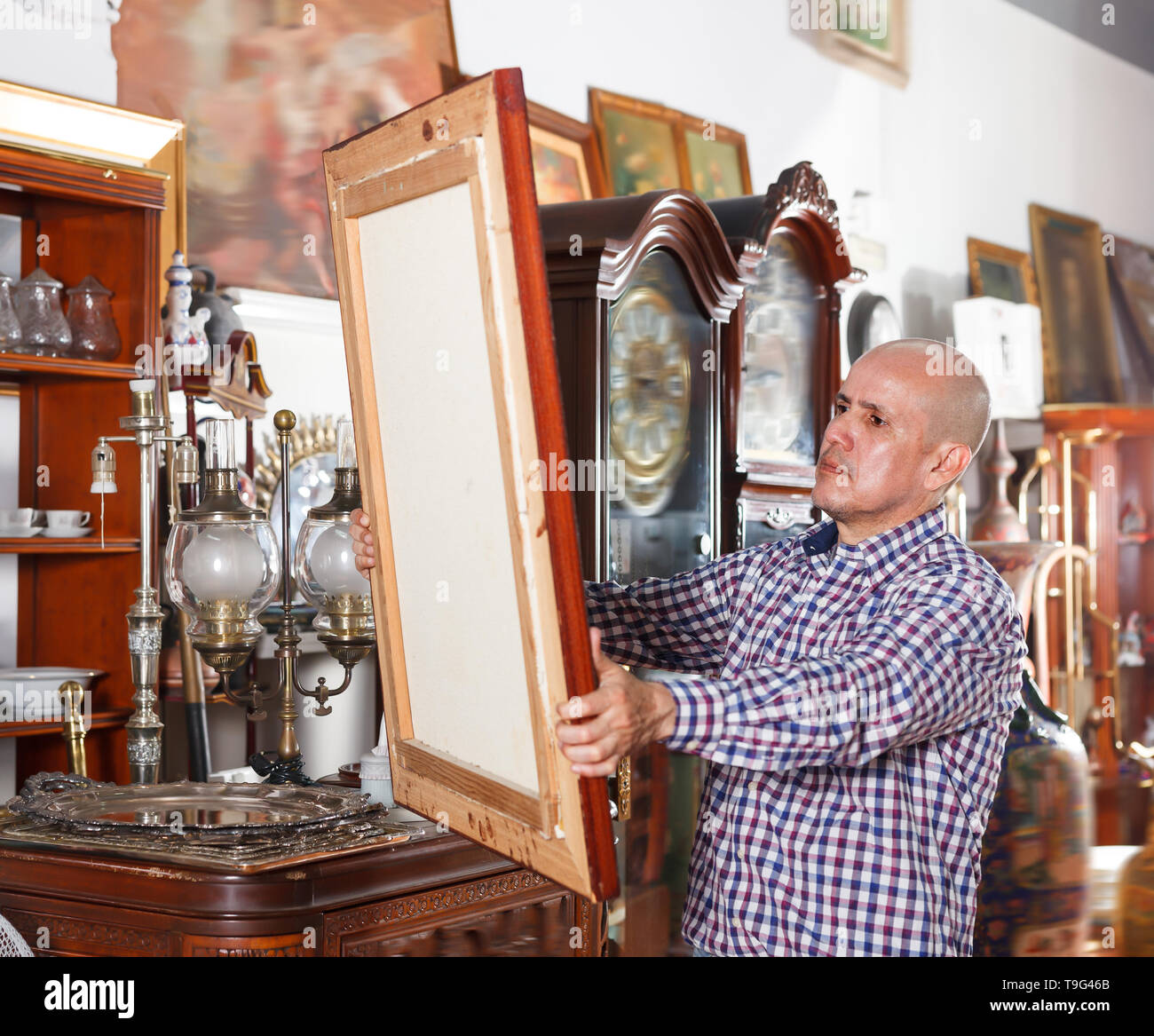 Ordinary male carefully examining antiques in store - Stock Image