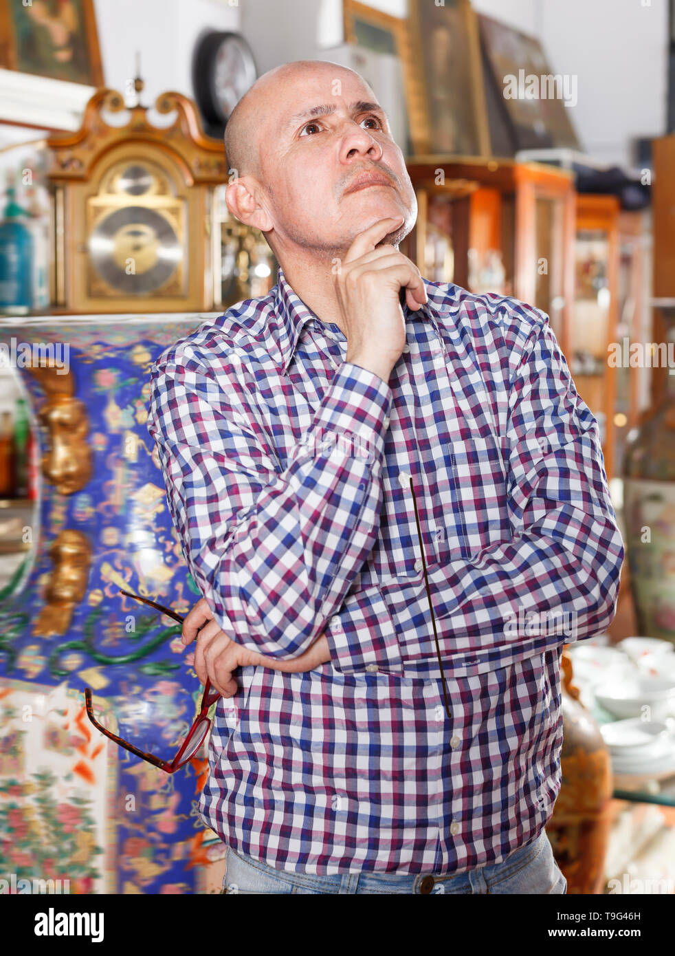 Intelligent male carefully examining antiques in store - Stock Image