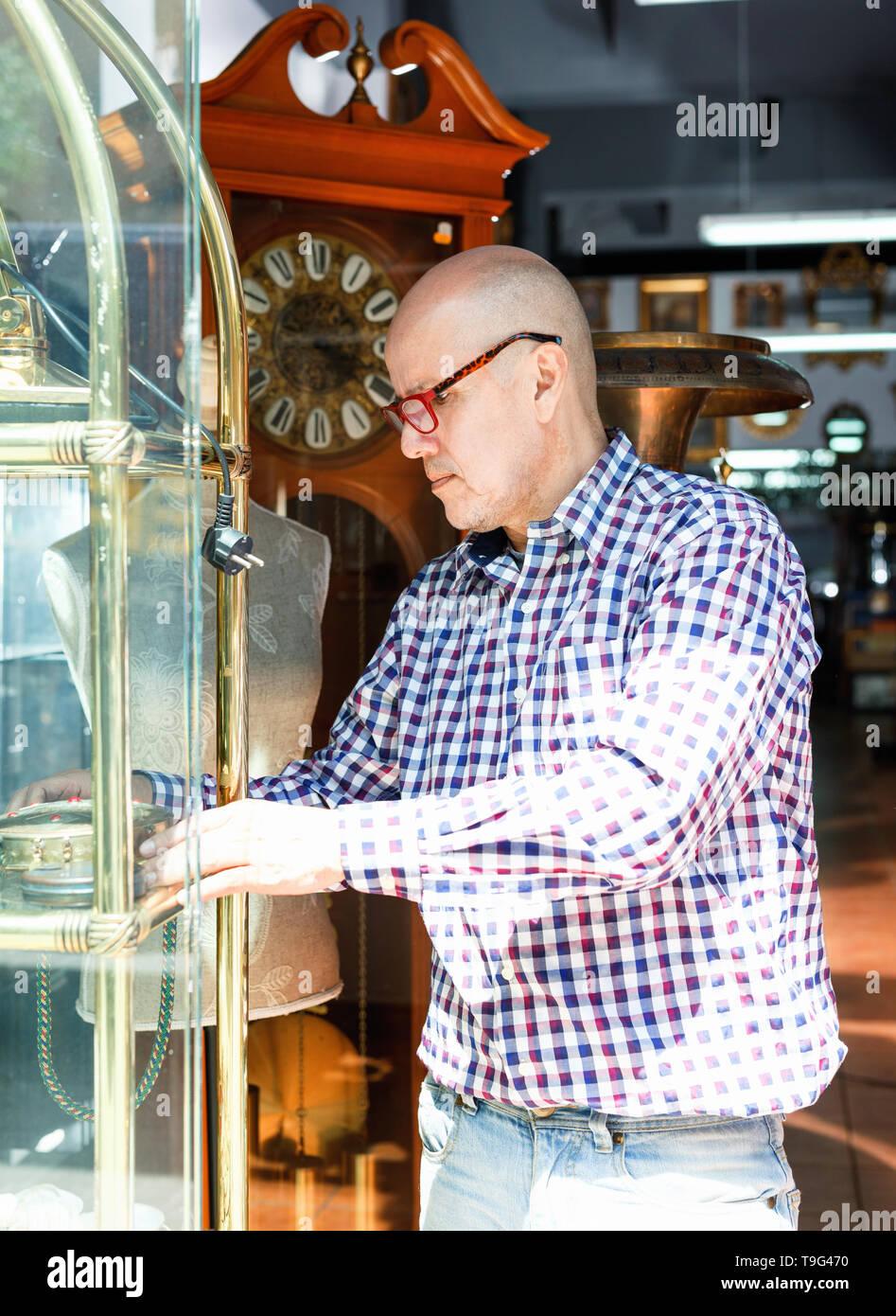 Portrait of mature pleasant positive friendly man choosing vintage goods at antiques shop - Stock Image