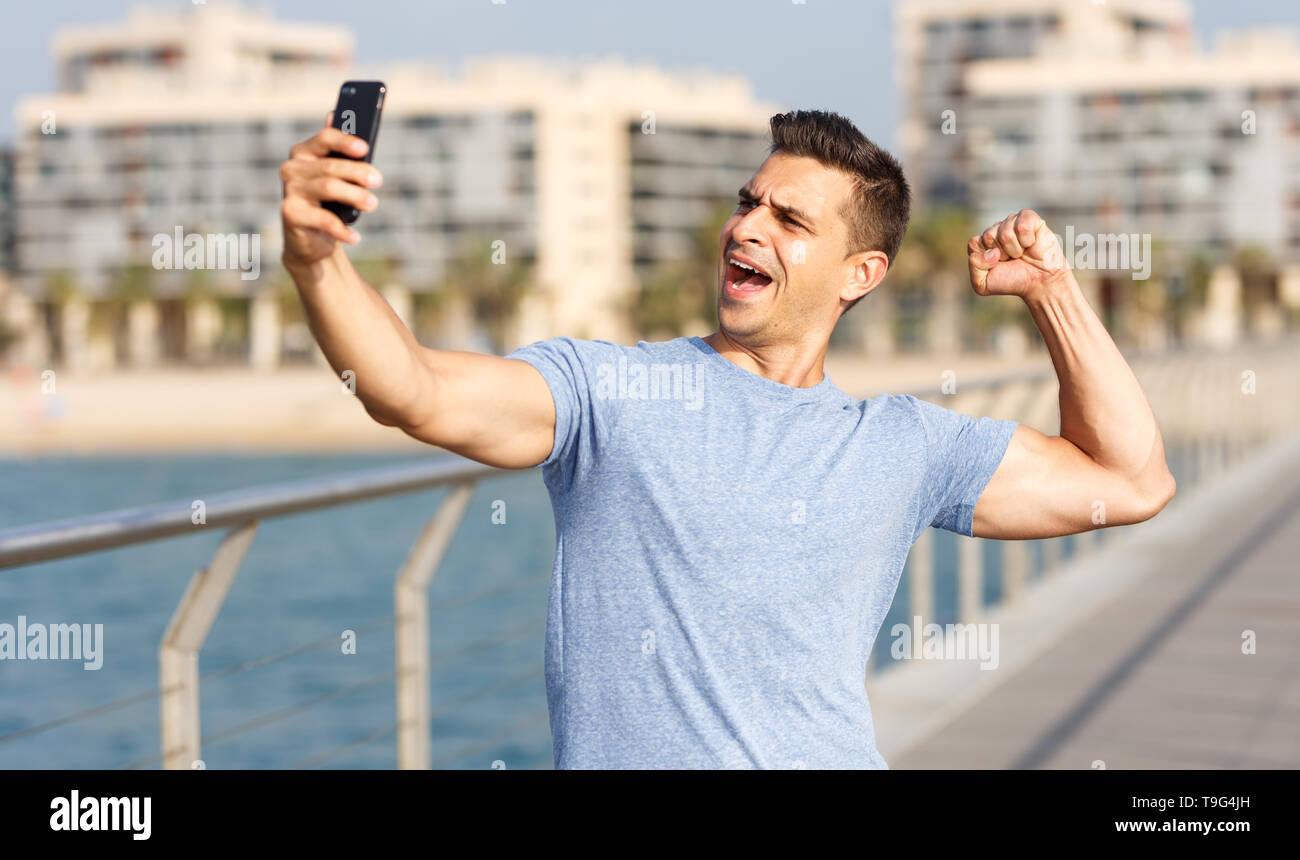 Positive sporty man taking selfie during workout outdoors - Stock Image